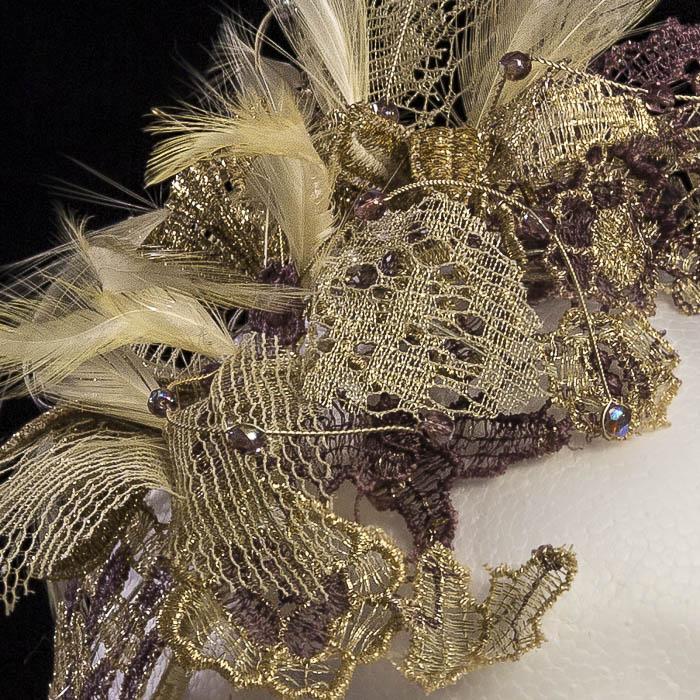 Tocado dorado de encaje y plumas, detalle