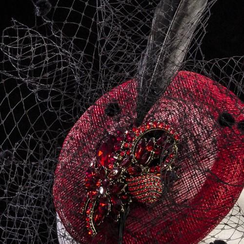 Tocado rojo y negro con pluma, velo y adorno, detalle