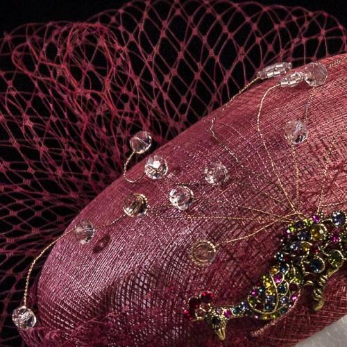 Tocado burdeos con adorno de metal y cristal, detalle